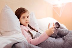 Sad little child sitting with a pillbox royalty free stock image