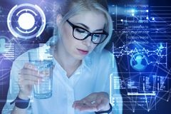 Young woman holding a glass of water while preparing to take pills. Necessary treatment. Clever calm attentive programmer sitting in front of a futuristic screen Stock Image