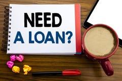 Necessidade escrita à mão da exibição do texto uma pergunta do empréstimo Crédito de hipoteca escrito no papel de nota do bloco d foto de stock