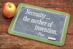 Necessity - the mother of invention. Plato quote on a slate blackboard against red barn wood stock photos