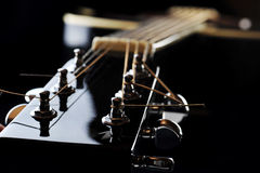 Neck of black guitar. Details of  acoustic black guitar. neck, nut, frets, strings Stock Images