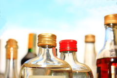 Neck bottles with different colored lids and alcohol Royalty Free Stock Photo