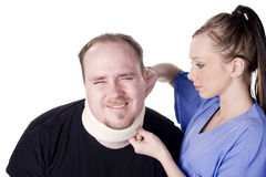 Neck Brace. Nurse applying neck brace on man in pain stock photography