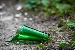 The neck of a broken green glass bottle lies on the street royalty free stock images