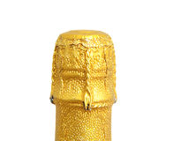Neck of closed champagne bottle. Packed in golden paper over white background Royalty Free Stock Photo