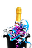 Neck of closed champagne bottle. Packed in golden paper witk cooler and party streamers over white background Royalty Free Stock Photography