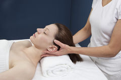 Neck decompressing massage. Female practitioner relaxing tensed cervicals Royalty Free Stock Photo