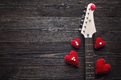 Neck Electric Guitar with hearts on a dark wooden background. Sp Stock Photo