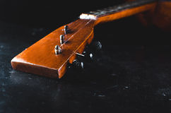 The neck of the guitar on a black. The neck of the Guitar, elegant on the black background, vintage grunge Stock Image