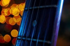 The neck of a guitar with strings and a rich blue light and bokeh stock photography