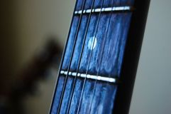 The neck of a guitar with strings and a rich blue light stock images