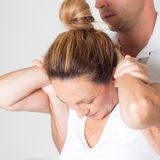 Neck manipulation. Doctor manipulating the neck of a female patient Royalty Free Stock Photo