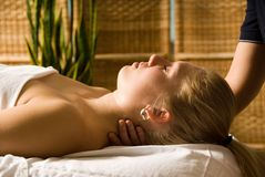 Neck massage. Woman in a day spa getting a neck massage royalty free stock images