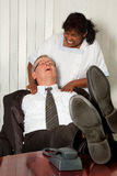 Neck massage in the office. Cleaning woman giving the manager of the office a neck massage stock photo