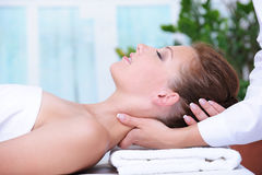 Neck massage for young woman. Relaxing in spa salon stock image
