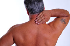 Neck pain. An older man rubbing the back of his neck stock image
