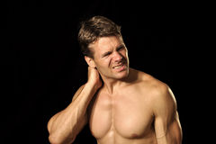 Neck pain. Muscular shirless male athlete suffers from acute neck pain stock photography