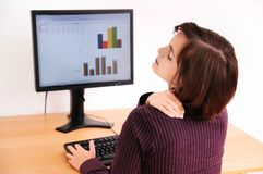 Neck pain - business person. Business woman with neck pain. Focus on hand on neck with blurred monitor on table. White wall in background Royalty Free Stock Image