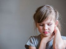 Neck pain. Portrait stressed unhappy child girl with back pain, Negative human emotions facial expression feeling. Neck pain. Portrait stressed unhappy child stock photography