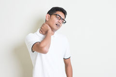 Neck pain. Portrait of tired Indian guy massaging his neck with painful face expression. Asian man standing on plain background with shadow and copy space Royalty Free Stock Photography