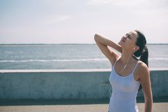 Neck pain during training. Athlete running Caucasian black hair woman runner with sport injury and touching upper back. Muscles outside after exercise workout Royalty Free Stock Image