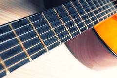 Neck, strings, sound box of a yellow and orange guitar. Stock Image