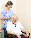 Neck Therapy - Ultrasound. Senior man getting ultrasound therapy on his neck, at the chiropractors office Stock Photo