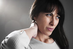 Neckache. Woman massaging neck, isolated on gray Royalty Free Stock Photo
