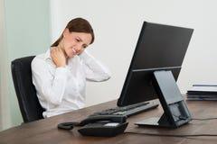 遭受Neckache的女实业家在书桌 免版税库存照片