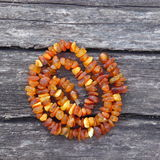 Necklace of amber beads. Bright orange amber necklace of raw beads on an old gray wooden background Stock Photos
