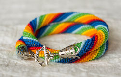 Necklace from beads of a rainbow colors on a textile background Stock Photo