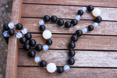 Necklace of black and moonstone beads. On the wooden surface Royalty Free Stock Image