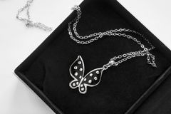 563cc63a9d77b8 Black silver butterfly pendant in black jewel box closeup stock images