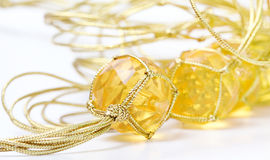 Necklace with cheap plastic gems with golden colored rope Royalty Free Stock Photos