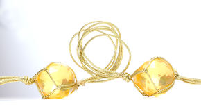 Necklace with cheap plastic gems with golden colored rope Stock Images