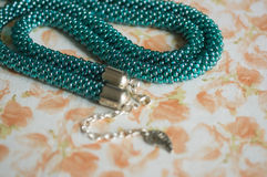 Necklace of color aquamarine from beads against a flower print Stock Image