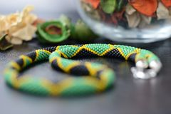Necklace in colors of Jamaican flag on a dark background. Close up royalty free stock image