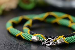 Necklace in colors of Jamaican flag on a dark background. Close up royalty free stock photos