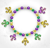 Necklace with Fleur de Lis. Necklace of purple, green, yellow beads, decorated with  Fleur de Lis Stock Photos