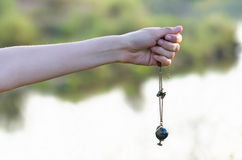 Necklace in the form of globe and binocular. Hand holding a necklace in the form of globe and binocular on natural background royalty free stock photos