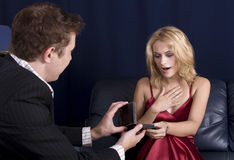 Necklace gift. Man holding out necklace in box to a beautiful young blond girl while Royalty Free Stock Photography