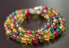 Necklace from glass beads of different colors on a dark surface Royalty Free Stock Image