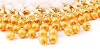 Necklace of gold pearls on a white bacground Royalty Free Stock Image