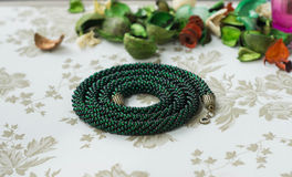 Necklace from green beads on a textile background Stock Photo