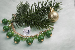 Necklace with green stones on a branch of a Christmas tree with a ball on an abstract background Stock Photography