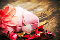 Necklace on heart symbol next to the pink box. Royalty Free Stock Photos