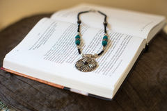 Necklace laying on the book Royalty Free Stock Image
