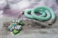 Necklace of mint color on a textile background Royalty Free Stock Image