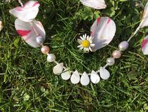 Bride White Mother of Pearl necklace. Necklace with mother of pearl beads with daisies and petals on grass background Stock Photos