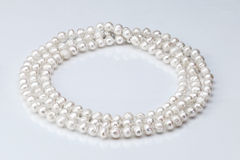 Necklace of pearls. On a white glossy background Royalty Free Stock Photos